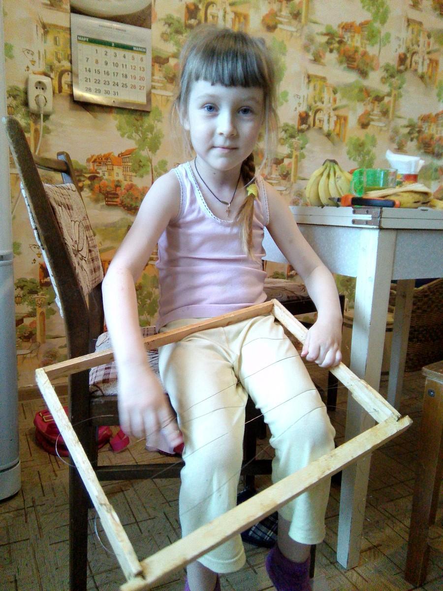 моя дочь помогает натягивать проволоку в рамках